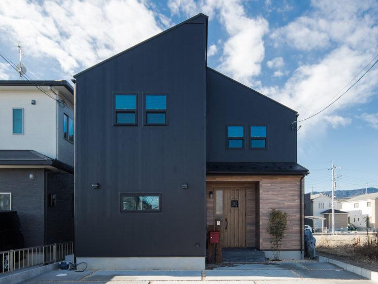 黒い外壁に板張り風の外観が目を惹くお家